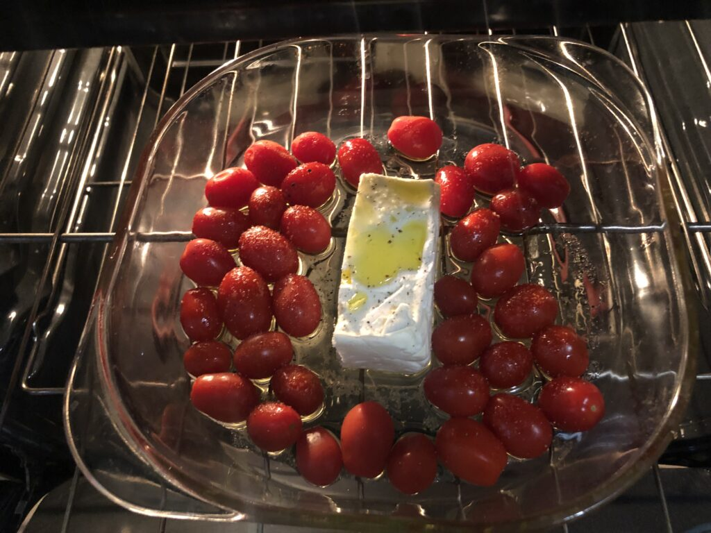 Cherry tomatoes, feta cheese block, salt, pepper, and olive oil on a baking sheet inside the oven. By: Stella González Pérez